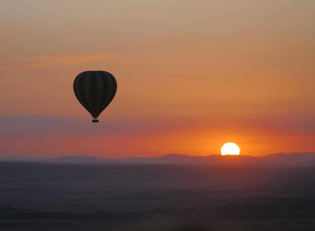 Sunrise behind a hot air balloon over the Maasai Mara