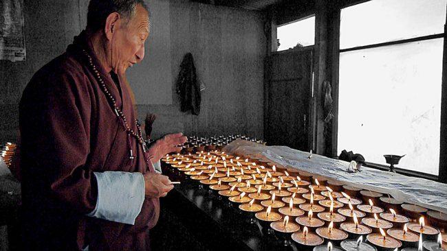 Lighting butter lamps in Bhutan