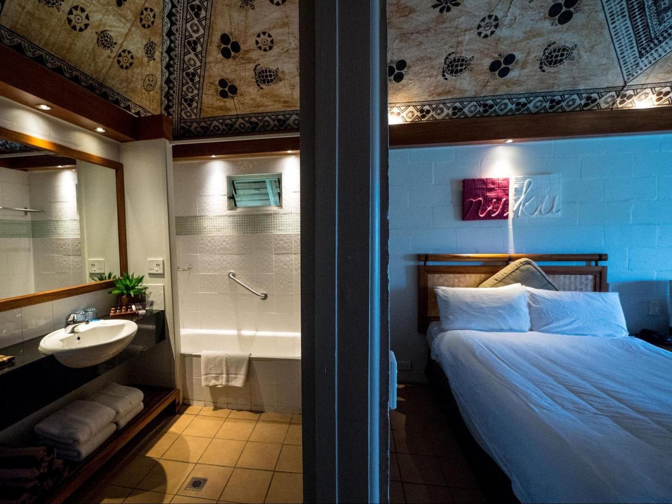 The bathroom and bedroom in the plantation bure at Outrigger Fiji Beach Resort