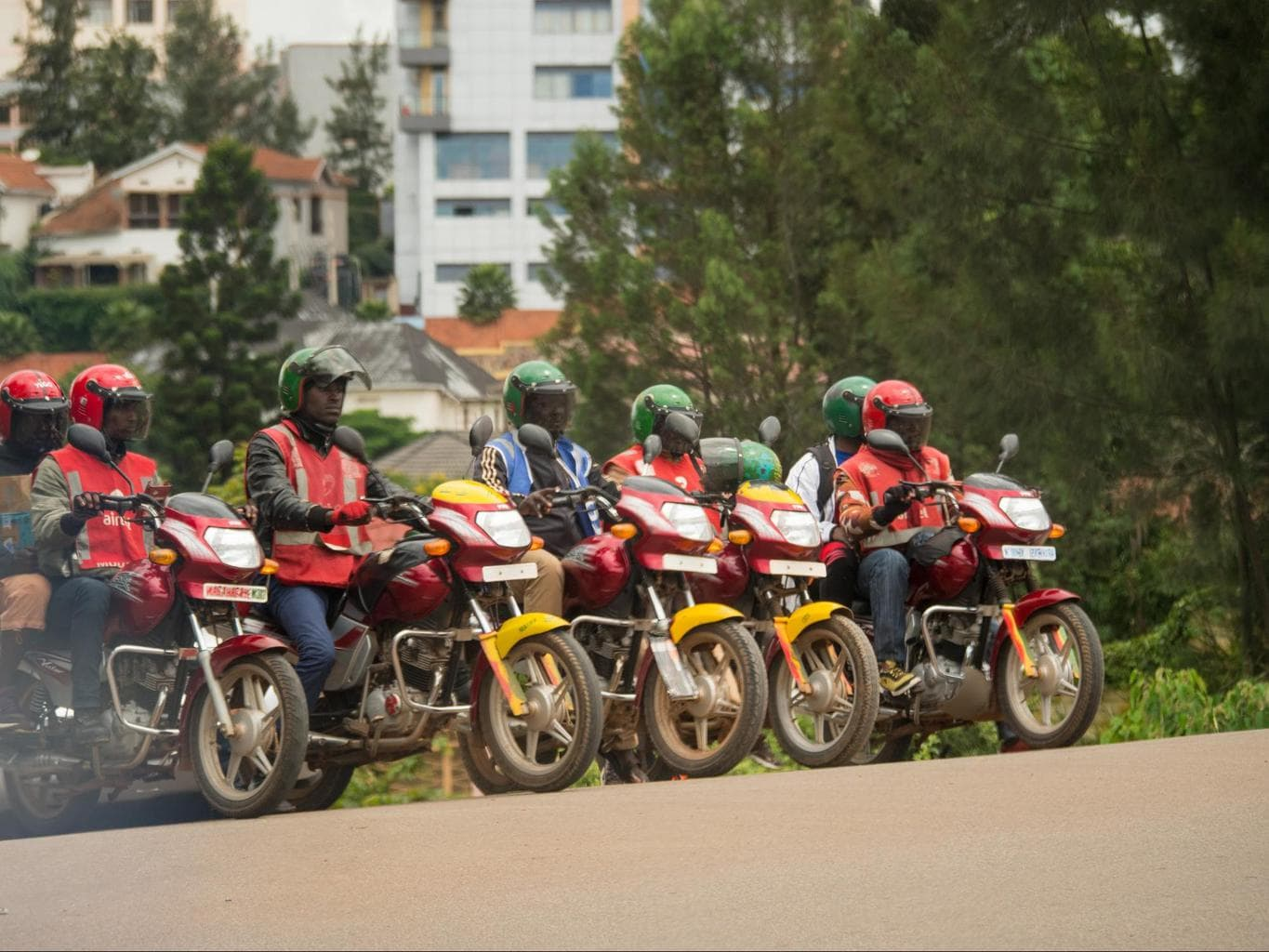 Boda Boda with helmets, passenger helmets hanging off the side, reflective vests and proper motorbikes