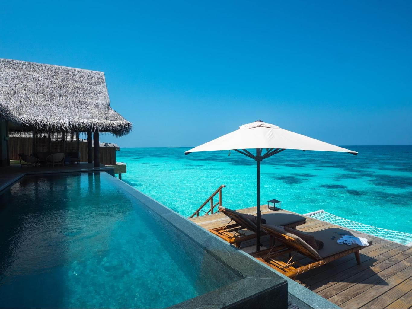 The pool and sun loungers at Joali's Luxury Water Villa