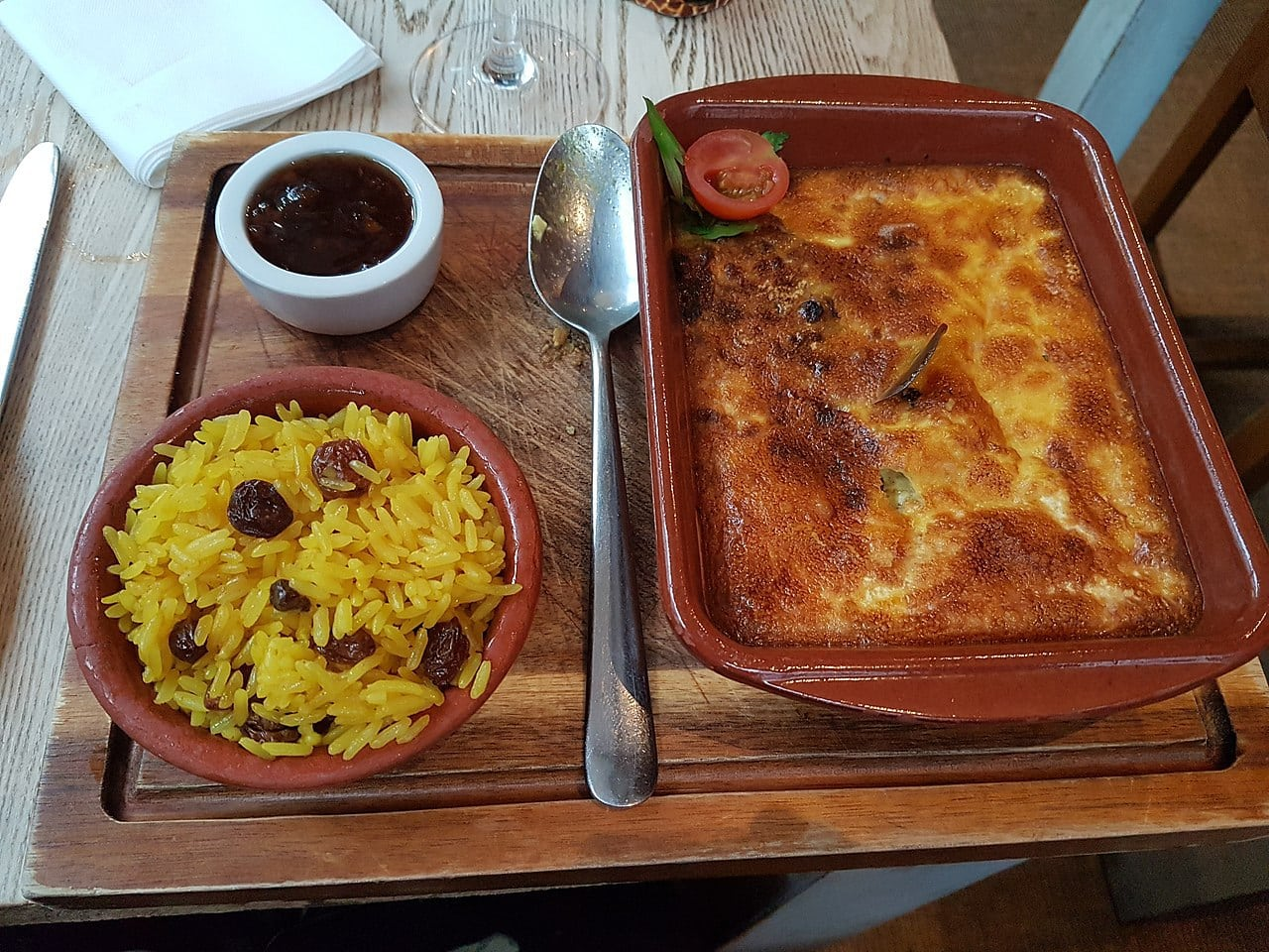 Bobotie with a side of yellow rice and some Mrs Ball's chutney. Wikipedia CharmaineZoe's Marvelous Melange (CC BY 2.0)